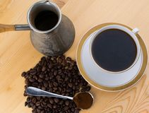Copo branco na colher do turco dos pires com café à terra e feijões de café na tabela de madeira Foto de Stock