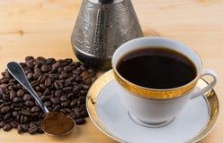 Copo branco na colher do turco dos pires com café à terra e feijões de café na tabela de madeira Imagem de Stock Royalty Free