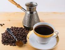 Copo branco na colher do turco dos pires com café à terra e feijões de café na tabela de madeira Fotografia de Stock Royalty Free