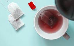 Copo cerâmico com os saquinhos de chá vermelhos do chá e do papel do fruto A água quente é Imagem de Stock Royalty Free