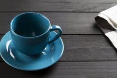Copo cerâmico para o café da cor azul sem líquido no fundo de madeira preto e o pano de listras cinzentas e brancas fotos de stock