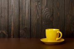 Copo cerâmico para o café e o chá da cor amarela em uma obscuridade de madeira Imagens de Stock Royalty Free