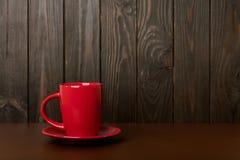 Copo cerâmico para o café e o chá da cor vermelha em um CCB de madeira escuro Imagens de Stock Royalty Free