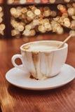 Copo com café derramado na tabela de madeira em uma cafetaria, fundo do borrão com efeito do bokeh foto de stock