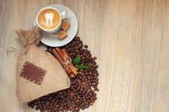 Copo com café com feijões de café, saco de serapilheira e canela no fundo de madeira claro fotografia de stock