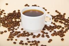Copo com café, grãos de café, um guardanapo Imagens de Stock