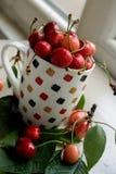 Copo com cerejas - folhas e cerejas ao redor Foto de Stock