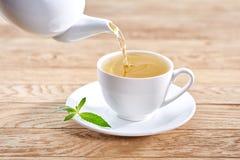 Copo com chá verde e bule no fundo de madeira branco da tabela Foto de Stock Royalty Free