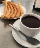 Copo com chocolate quente e placa dos churros foto de stock