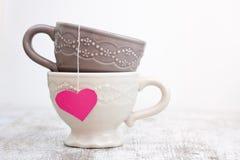 Copo com o saquinho de chá dado forma coração imagem de stock