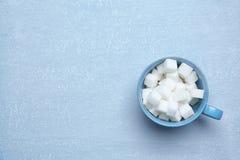 Copo com os cubos do açúcar refinado fotografia de stock