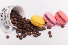 Copo com os feijões de café com os bolinhos de amêndoa franceses deliciosos coloridos no fim branco do fundo acima Imagem de Stock Royalty Free