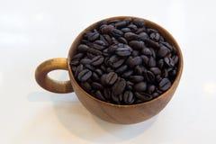 Copo com os feijões de café isolados no fundo branco fotos de stock