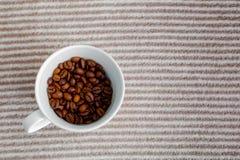 Copo com os feijões de café no fundo listrado cinzento fotografia de stock royalty free