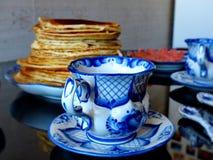 Copo com pires e colher de chá o estilo de Gzhel no fundo de panquecas do blinov do russo Celebração de Maslenitsa Gzhel imagem de stock
