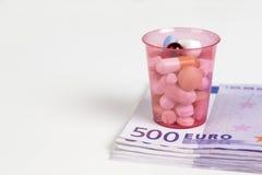 Copo com tabletts em uma pilha de 500 notas do Euro Foto de Stock Royalty Free