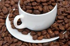 Copo com um saucer e os feijões de café Fotos de Stock Royalty Free