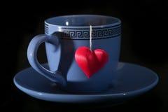Copo com uma sombra sob a forma do coração e de um coração em uma linha Foto de Stock Royalty Free