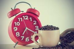 Copo cor-de-rosa com grão de café e um despertador vermelho Imagens de Stock Royalty Free