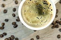 Copo da bebida quente com feixe na tabela de madeira, fim do café acima Foto de Stock