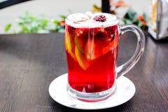 Copo da bebida quente do fruto e das bagas no vidro e na canela claros imagem de stock