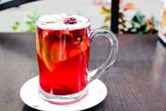 Copo da bebida quente do fruto e das bagas no vidro e na canela claros foto de stock