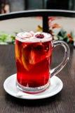 Copo da bebida quente do fruto e das bagas no vidro e na canela claros imagem de stock royalty free