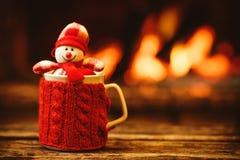 Copo da bebida quente na frente da chaminé morna Natal do feriado Fotografia de Stock