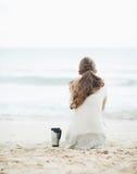 Copo da bebida quente perto da jovem mulher na camiseta que senta-se na praia Fotografia de Stock Royalty Free