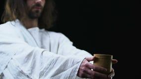 Copo da exibição de Jesus Christ de água à câmera, conceito pobre de ajuda da caridade dos povos filme