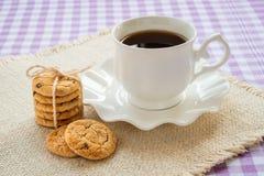 Copo da porcelana com chá em pires com borda e a pilha onduladas de cookies de farinha de aveia com partes de chocolate escuro ca fotografia de stock royalty free