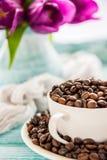 Copo da porcelana completamente de feijões de café e de flores cor-de-rosa no fundo chique gasto da hortelã, ponto de vista super Imagem de Stock