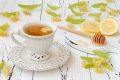 Copo da tisana com flores, limão e mel do Linden em um fundo de madeira velho Fotografia de Stock Royalty Free