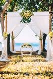 Copo de água, local de encontro da cerimônia na praia com detalhes da flor e vista para o mar Imagem de Stock