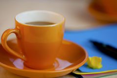 Copo de café alaranjado no papel de escrita marrom com pena Foto de Stock