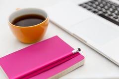 Copo de café amarelo e caderno cor-de-rosa brilhante no escritório moderno Imagens de Stock Royalty Free