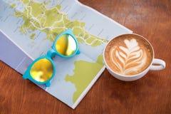 Copo de café branco com arte do latte com mapa do curso e óculos de sol o imagens de stock
