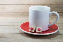 Copo de café branco com os cubos do açúcar mascavado no fundo de madeira imagem de stock royalty free
