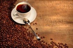 Copo de café branco com os feijões na tabela rústica Foto de Stock Royalty Free