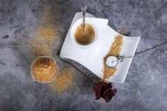 Copo de café branco da porcelana com o relógio do açúcar mascavado, do queque, do açucareiro, da rosa e de bolso fotos de stock royalty free
