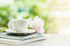 Copo de café branco em cadernos espirais com a flor doce da rosa do rosa fotos de stock