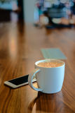 Copo de café branco na tabela de madeira na cafetaria Foto de Stock