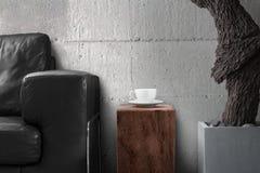 Copo de café branco na tabela de madeira na sala de visitas cinzenta Foto de Stock