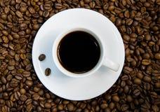 Copo de café branco nos feijões. Imagens de Stock Royalty Free