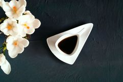 Copo de café cerâmico branco em uma textura concreta escura em um fundo do açafrão, espaço do vintage da cópia Imagem de Stock