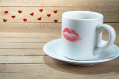 Copo de café cerâmico com marca do batom no fundo de madeira foto de stock
