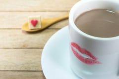 Copo de café cerâmico com marca do batom no fundo de madeira imagens de stock