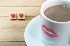 Copo de café cerâmico com marca do batom no fundo de madeira imagem de stock