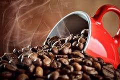 Copo de café cerâmico vermelho que encontra-se nos feijões de café quentes imagem de stock