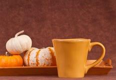 Copo de café com abóboras fotografia de stock royalty free
